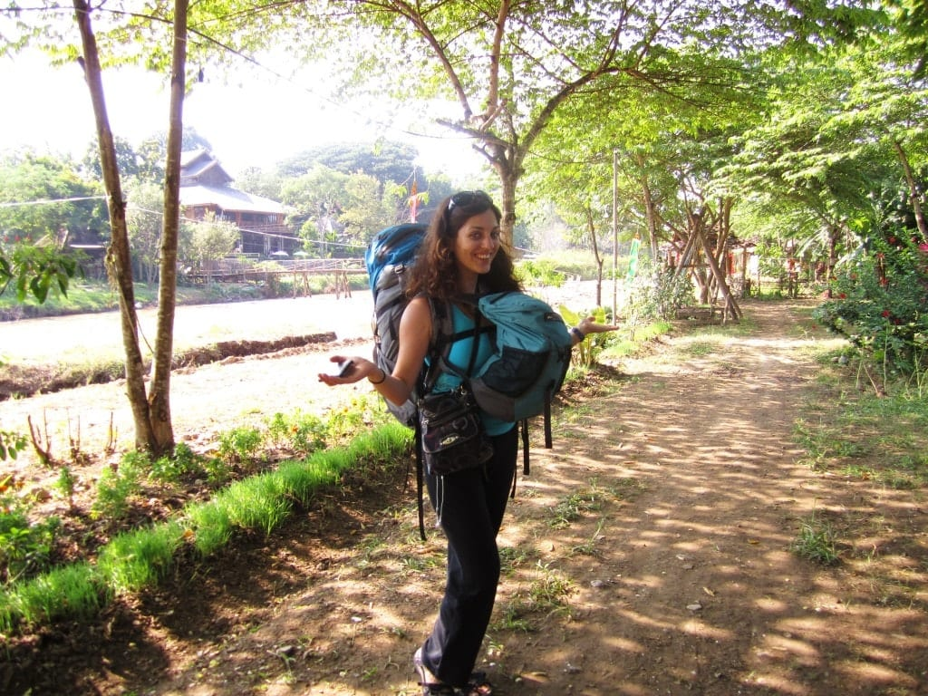Kate at age 26 in 2010, wearing a large backpack on her back and a small backpack in front, double turtle style, standing on a wooded path in Pai, Thailand.