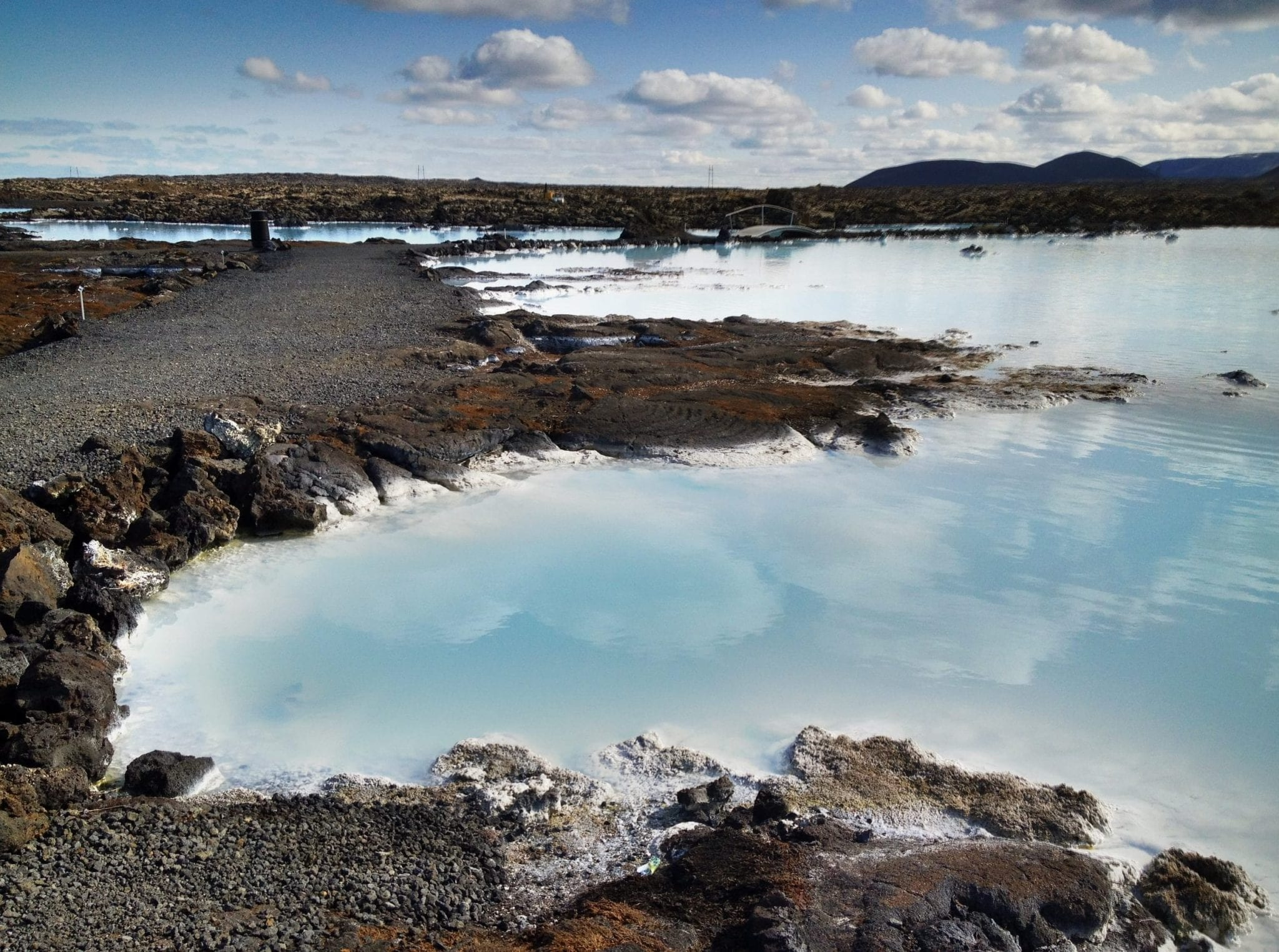The milky Blue Lagoon in Iceland, edged by rocky gray coastline, underneath a blue sky.
