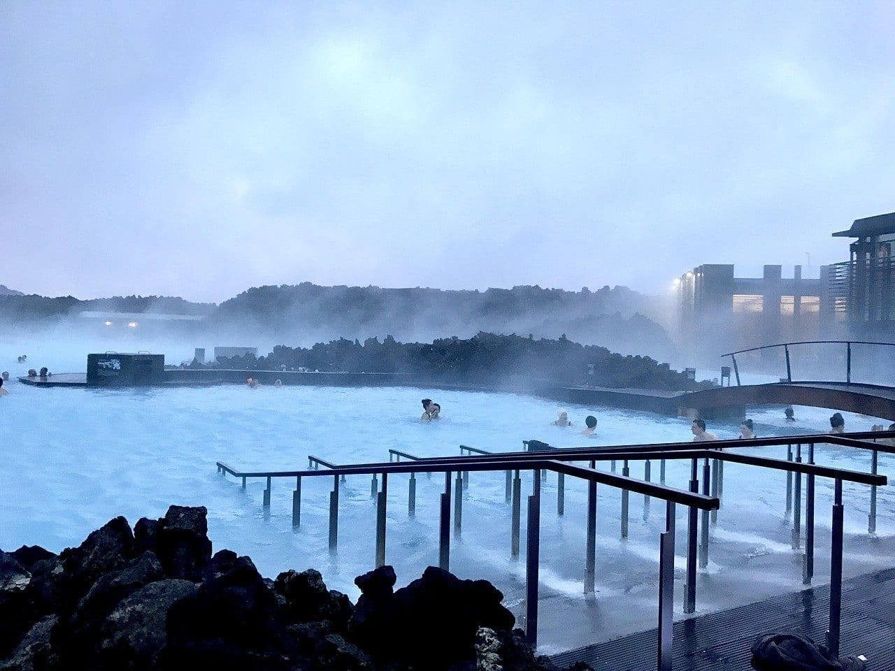 People swimming in Iceland's Blue Lagoon at dusk, steam rising up from the milky blue waters.