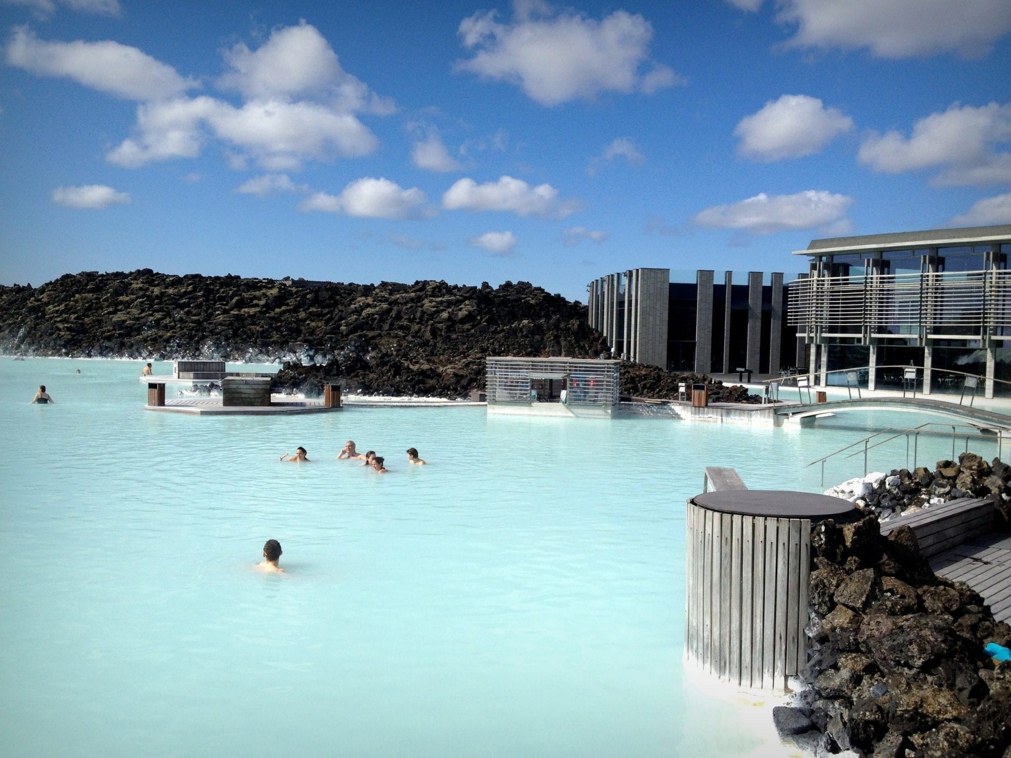 In Iceland, the Blue Lagoon -- pale turquoise milky water with people swimming in it, underneath a bright blue sky with clouds.