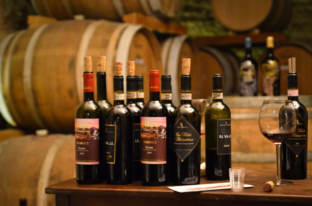 Several wine bottles lines up on top of a wine barrel, more wine barrels in the background.