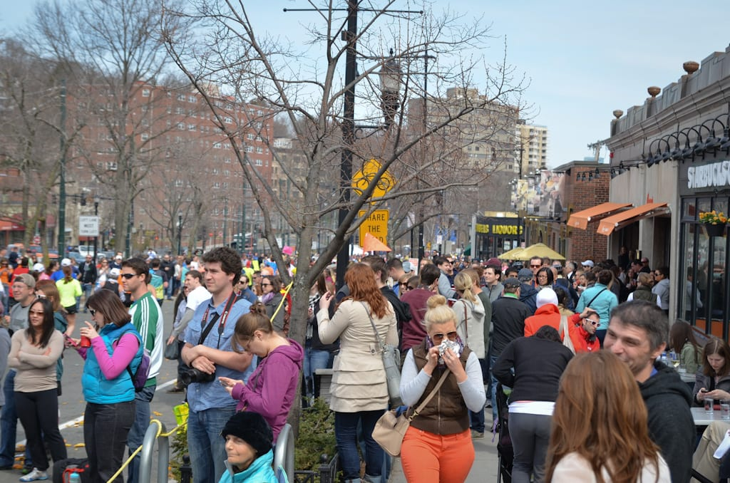 People waiting on the sideline of the Boston Marathon, surrounded by storefronts, in Washington Square, Brookline.