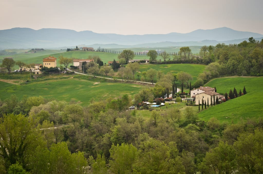 The Val d'Orcia in the Tuscan countryside -- rolling hills, a small farmhouse, pointy cypress trees, and mountains in the distance, on a gray foggy day.