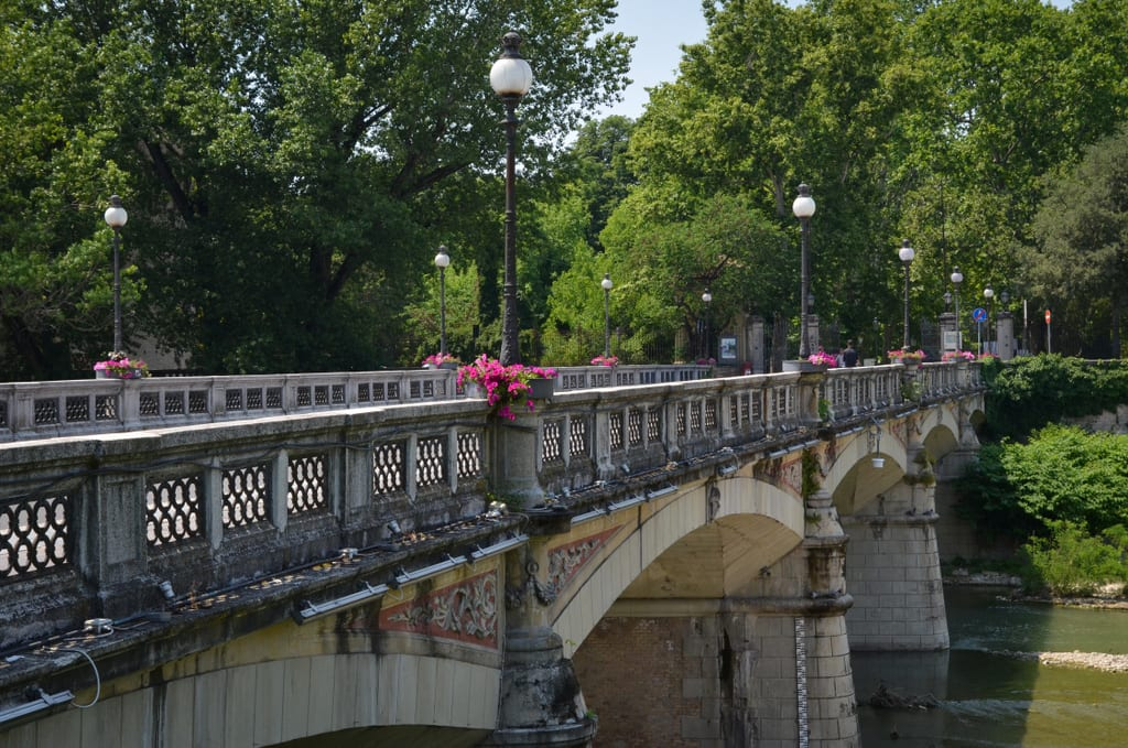 The Verdi bridge in Parma, gray stone and iron, topped with pink flowers.