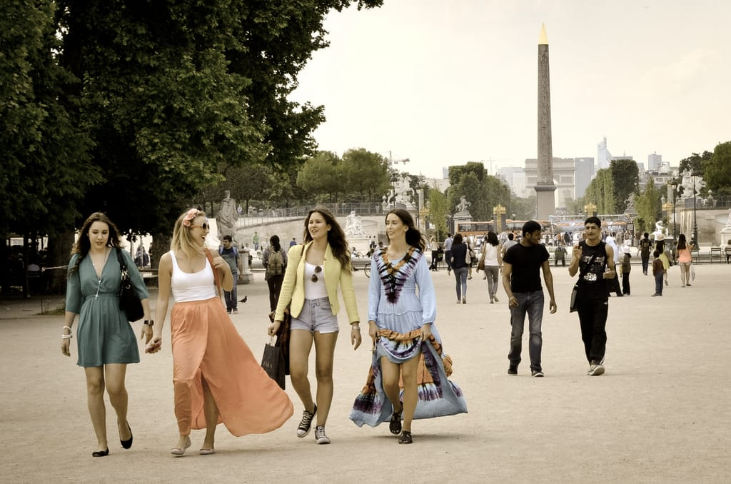 Four women walking through the Tuileries Gardens in Paris, all wearing fashionable and colorful dresses.