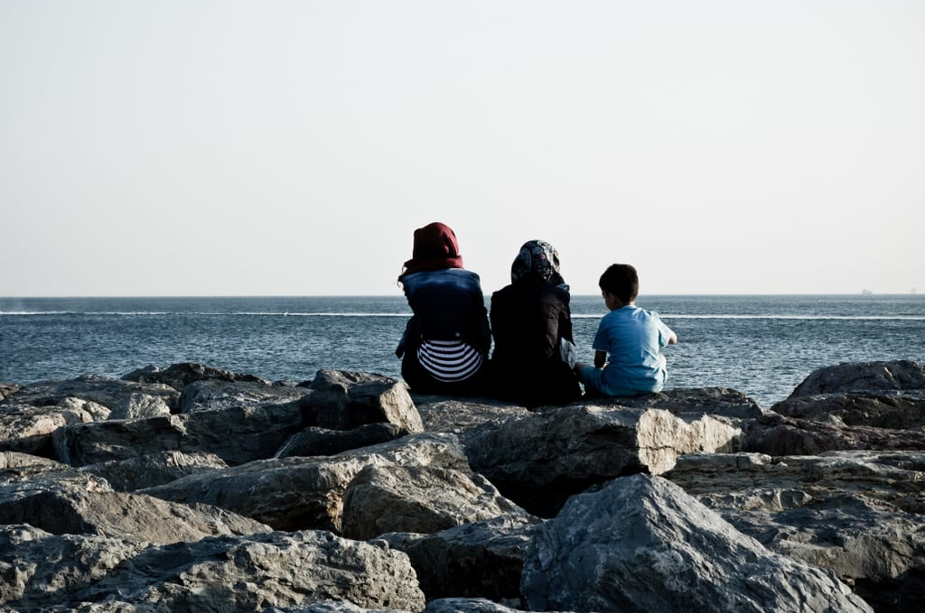 Two women and a child sitting on the rocky barrier to the Bosphorus, facing away.