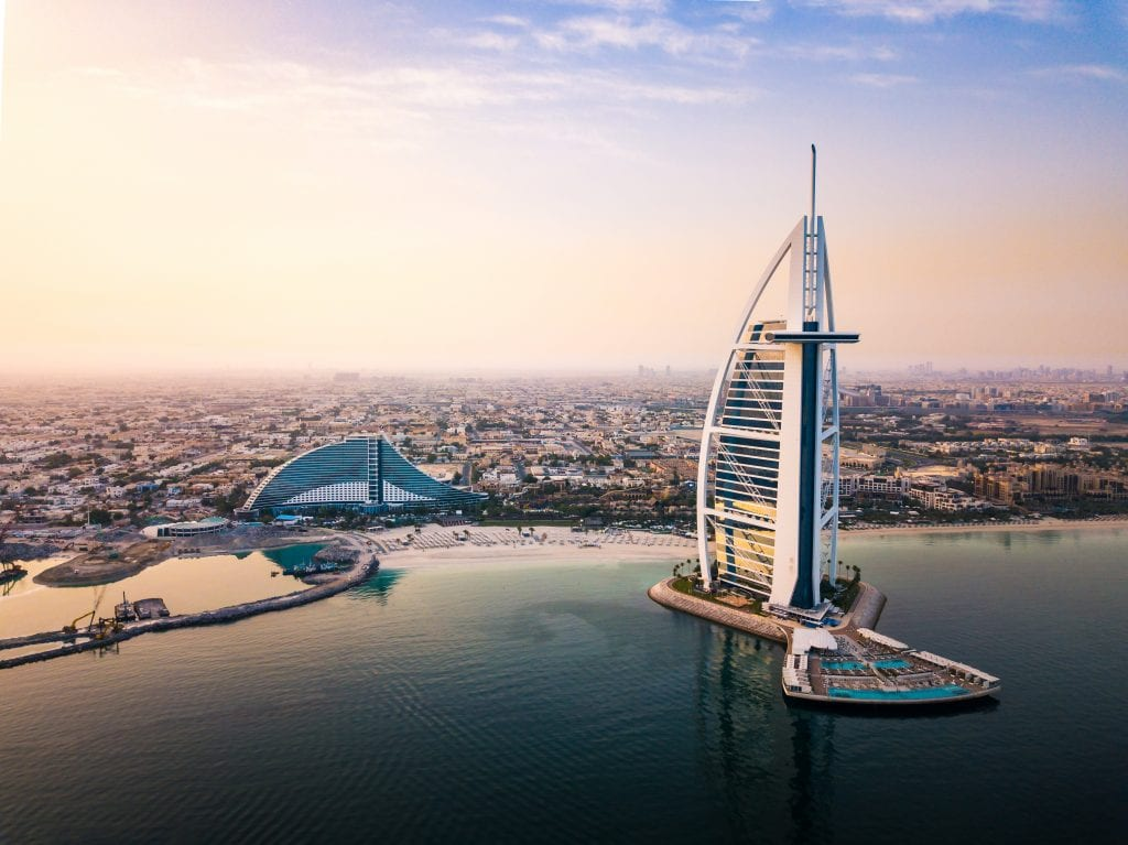 The giant, sail-shaped white Burj al Arab hotel in Dubai, looking like it's coming out of the water. In the distance you see the rest of Dubai in early evening violet.