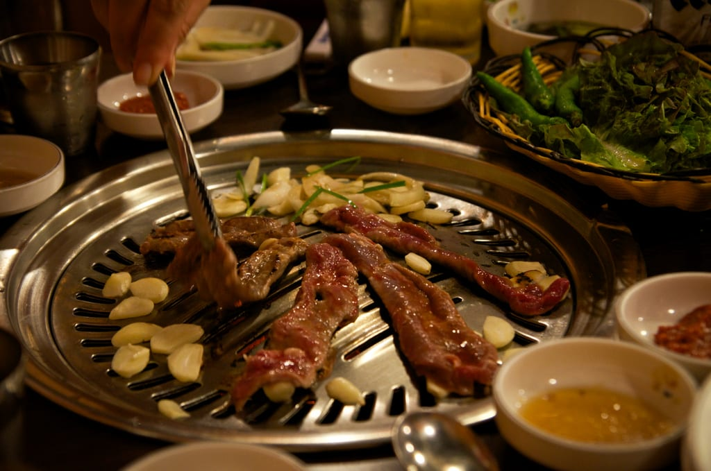 Strips of sizzling steak on a Korean barbecue.