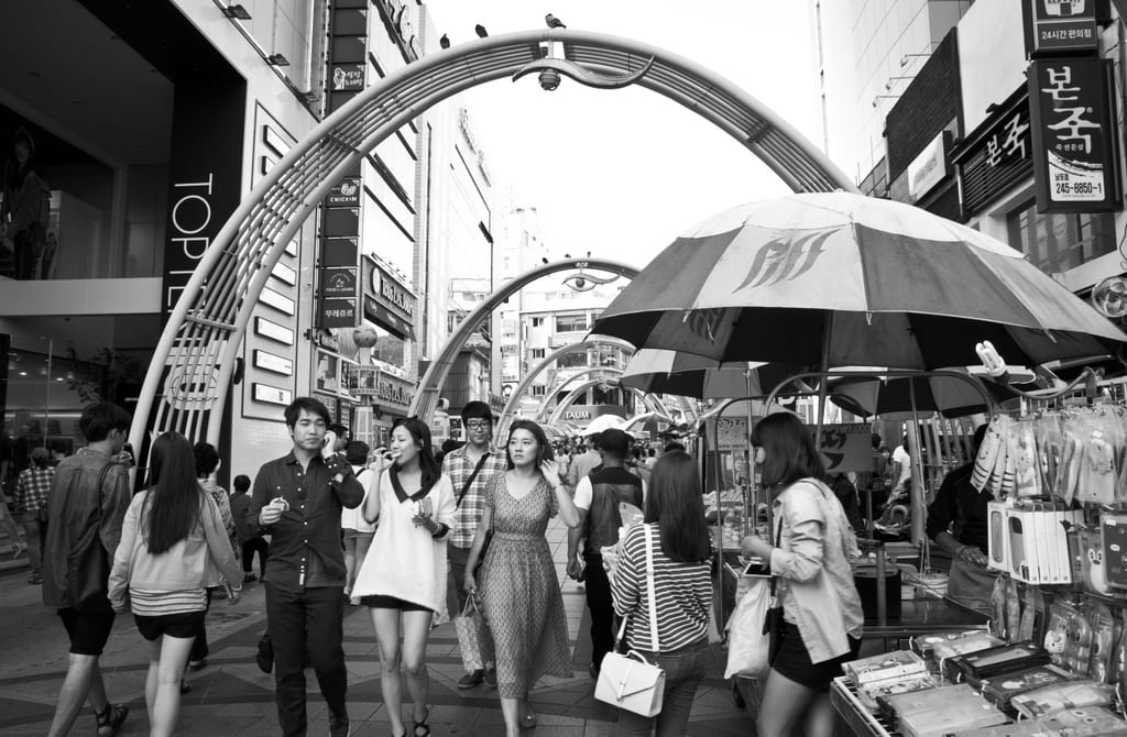 A black and white shot of people shopping on a street in Busan, Korea