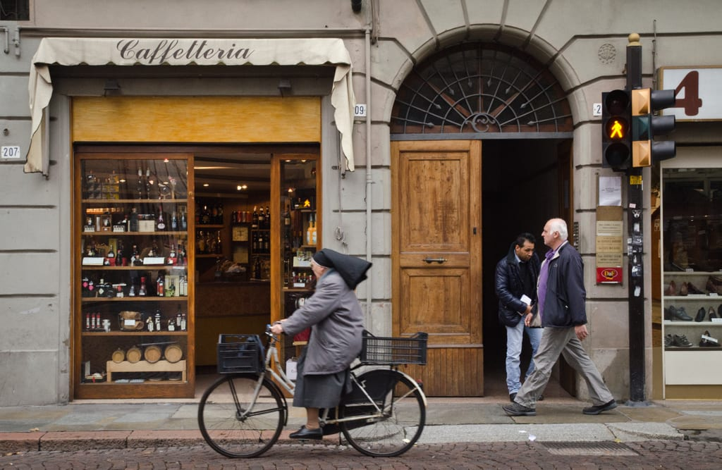 In the city of Modena, a nun wearing a black habit rides by on a bicycle while looking into the open door of a wine shop.