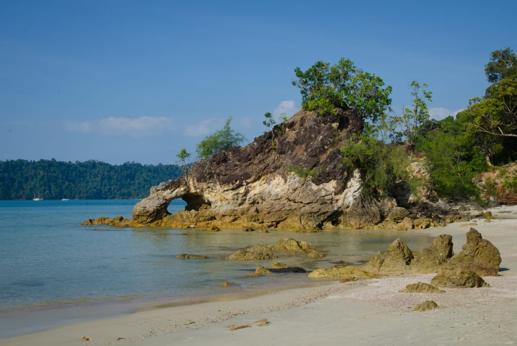 A beach with bright blue water in Koh Phayam, Thailand.