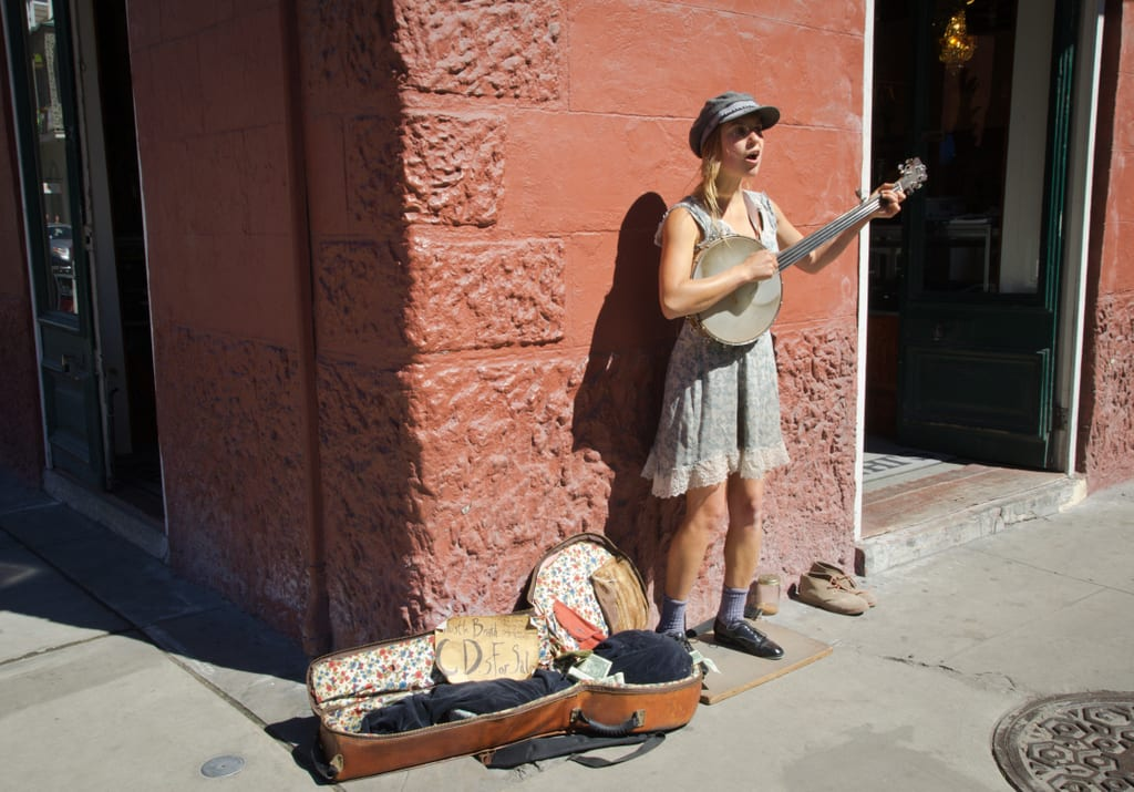 A woman wearing a dress and playing a small guitar on a street in New Orleans, an open case on the ground next to her for tips.