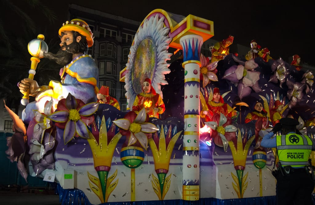 A big colorful float with flower patterns made out of cardboard on a Mardi Gras parade.