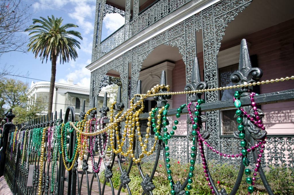A pink house with black wrought-iron detailing on the porch. In the foreground you see a black spiky French with purple, green and gold Mardi Gras beads draped over it.