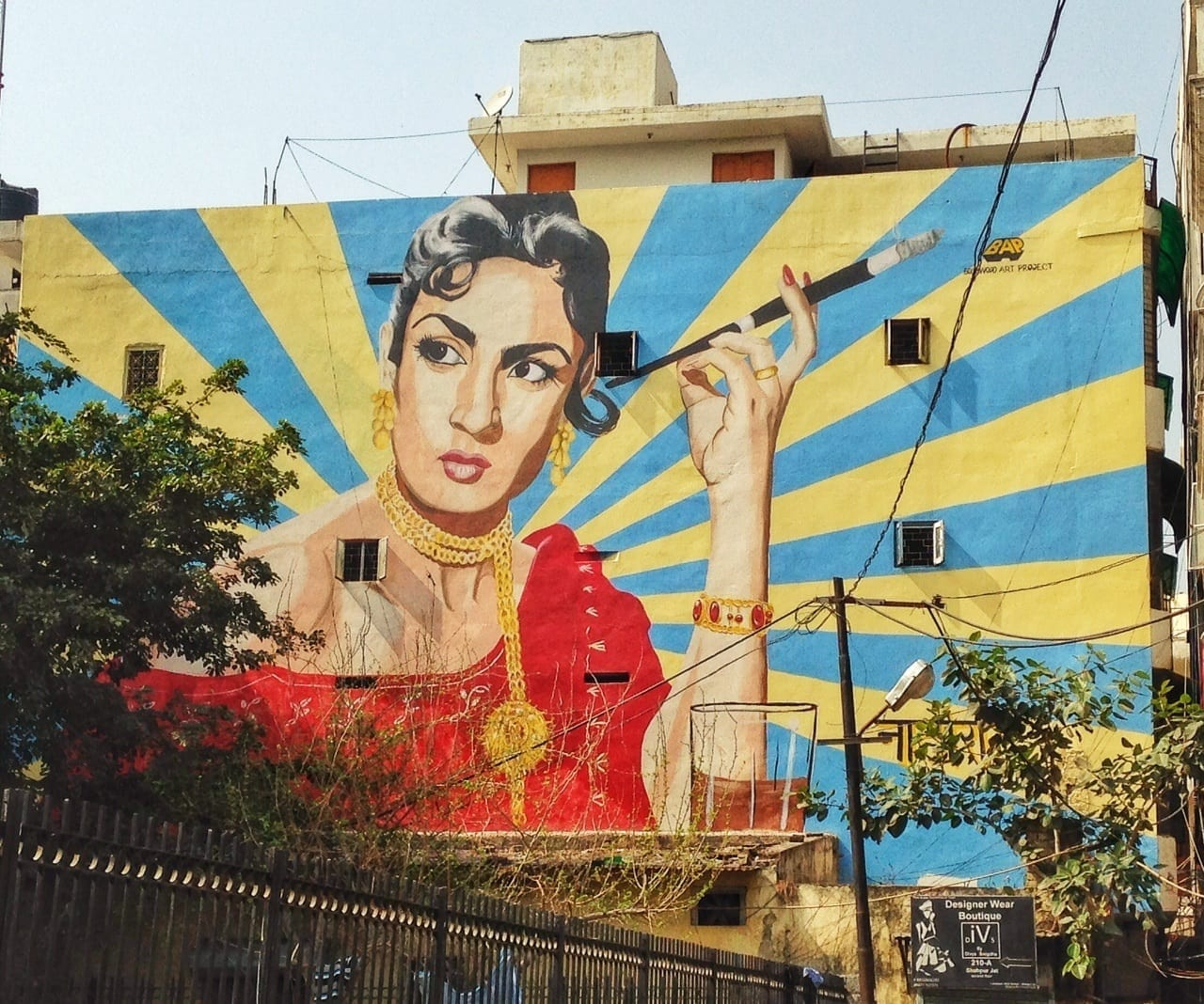 A mural in Delhi featuring a woman in a red dress holding a long cigarette holder.