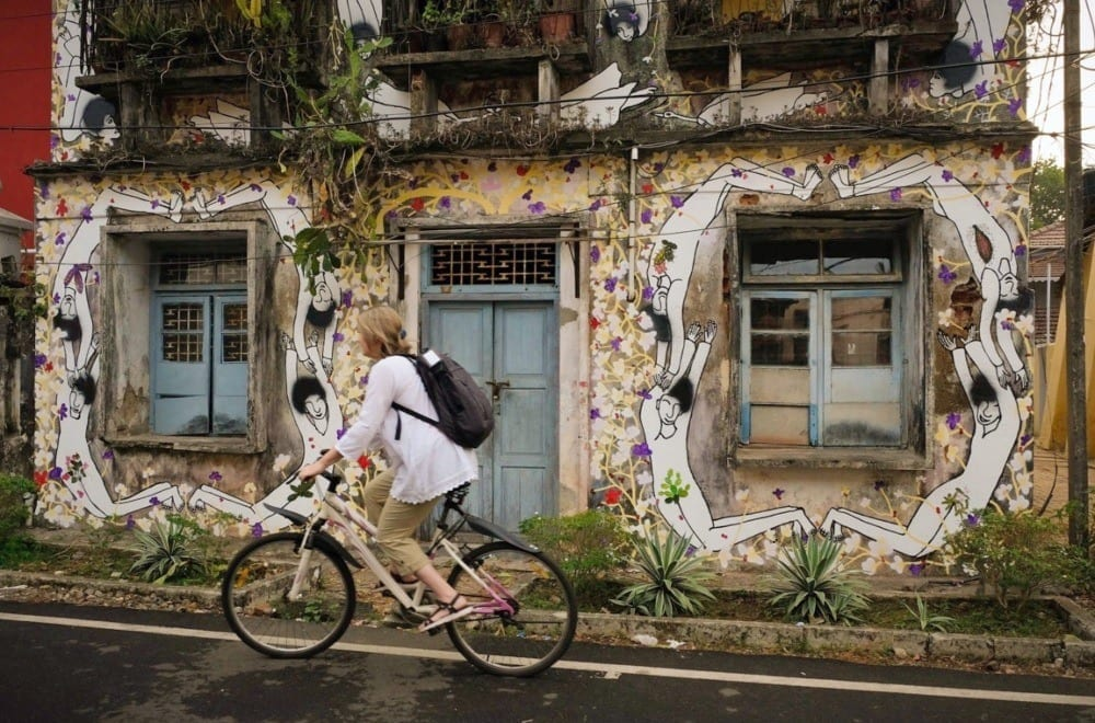 Blonde woman riding a bicycle against a painted wall with a blue door in Kochi, India.