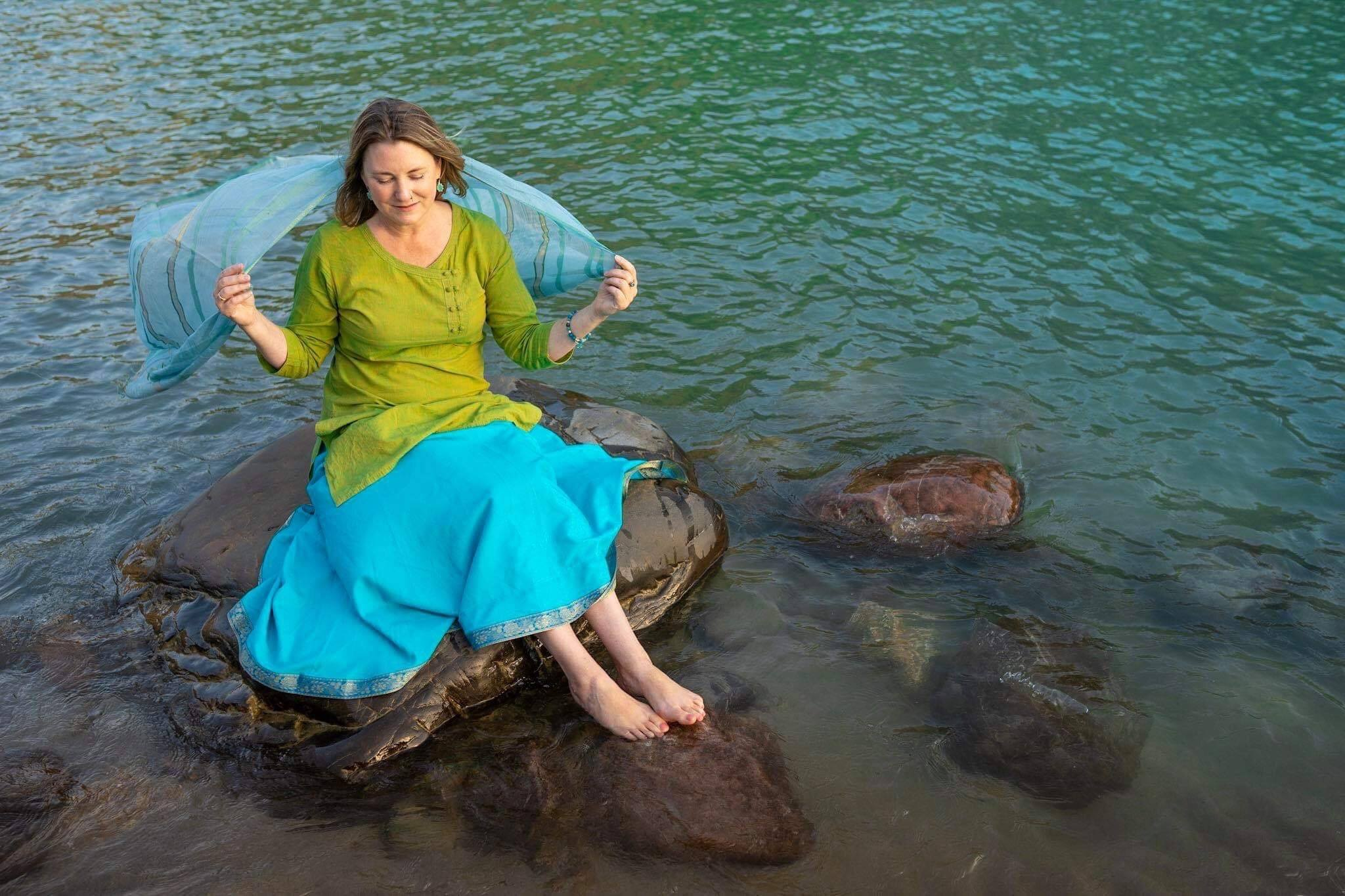 Mariellen Ward in a green and blue dress holding a blue shawl behind her, sitting on a rock in the Ganga river.