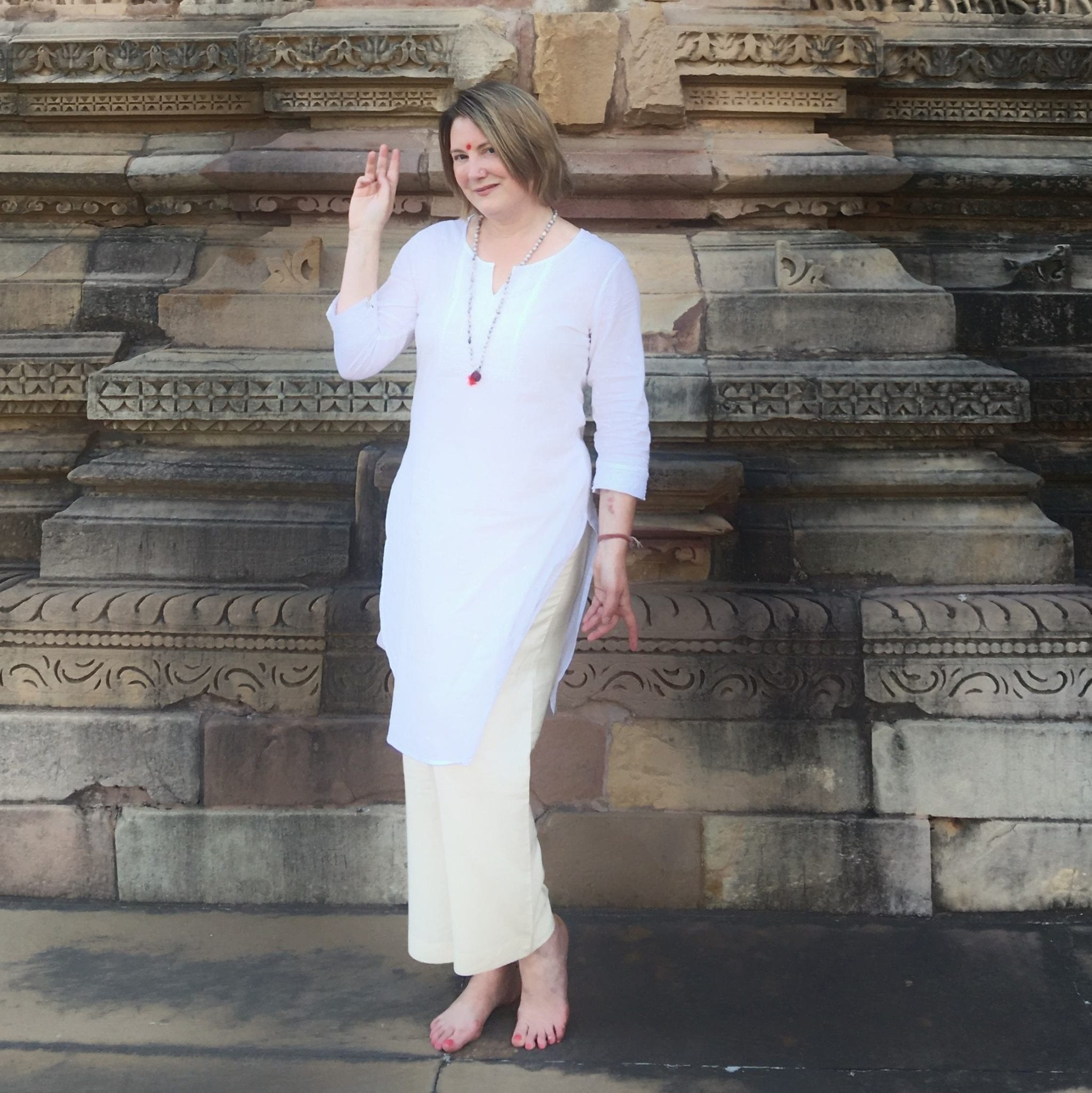 Mariellen Ward wearing a white top and tan trousers, posing in a temple in Khajuraho, India.