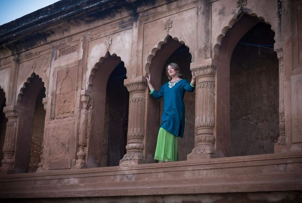 Mariellen Ward in a navy top and bright green skirt in a temple opening in Lucknow, India.