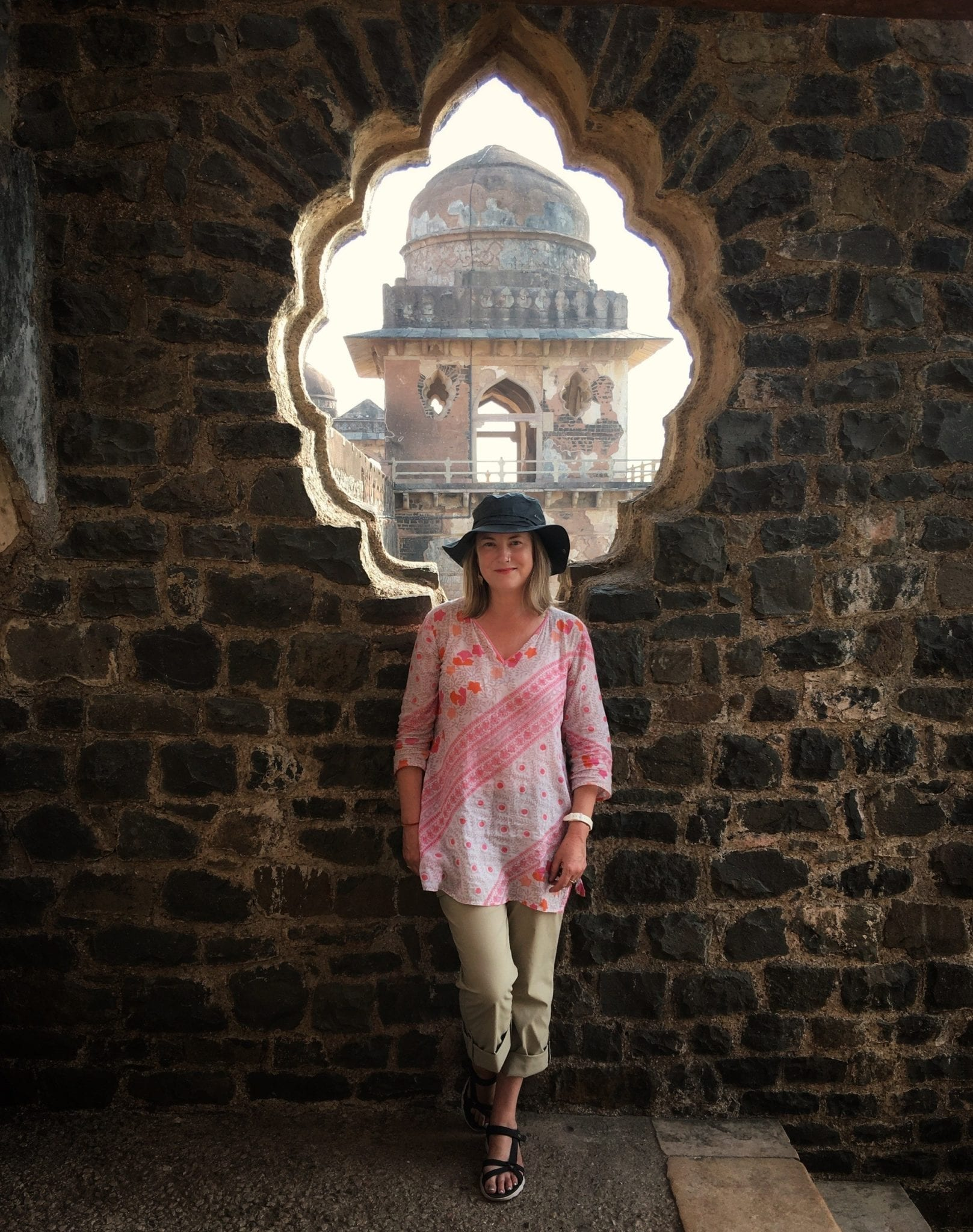 Mariellen Ward wearing a white and red top and black hat and posing in front of a scalloped window opening in a temple in Mind, India.