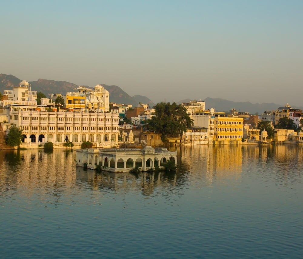 The golden city of Udaipur, Rajasthan, India, rests on the blue river at dusk.