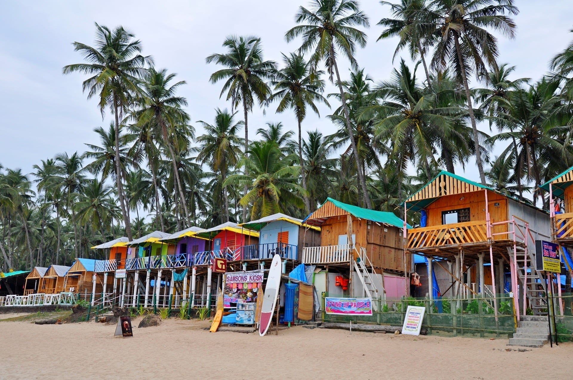 A line of brightly painted beach shacks beneath palm trees on the sand in Goa, India.