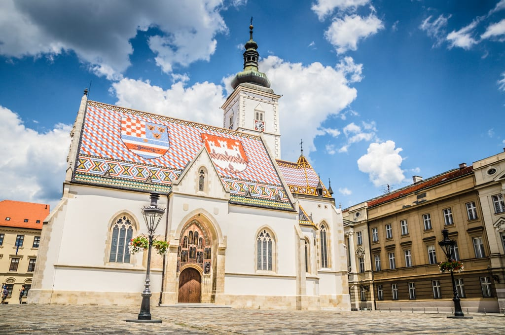 A church in Zagreb topped with orange , blue, and white tiles in a pattern underneath a bright blue sky with clouds.