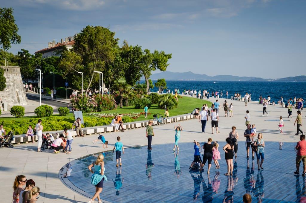 People walking across a blue disk -- the sun salutation -- on the gray boardwalk in Zadar, Croatia, trees on the left side.
