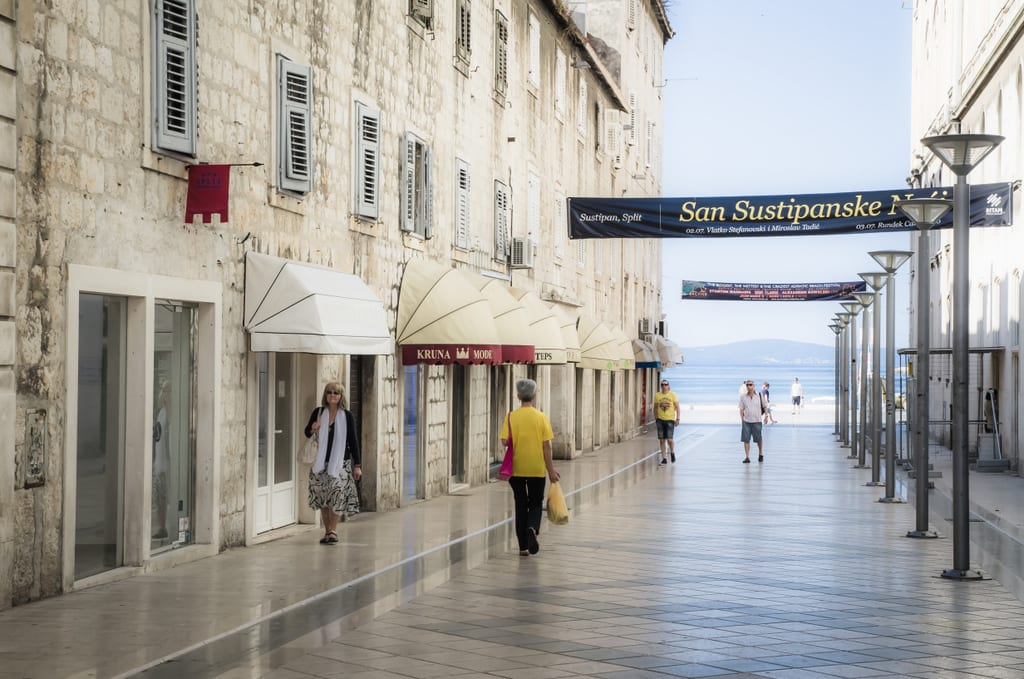 A quiet street in Split early in the morning surrounded by pale gray stone buildings, the ground so smooth it's reflective, the sea in the distance.