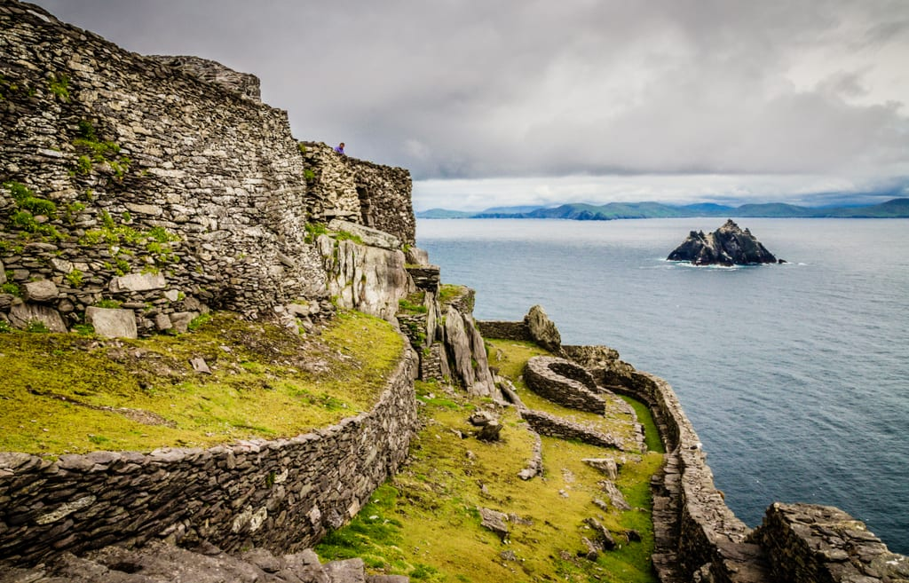 View from Skellig Michael: a craggy green Ireland covered with stone walls. In the distance you see a small island in the sea underneath a gray cloudy sky.