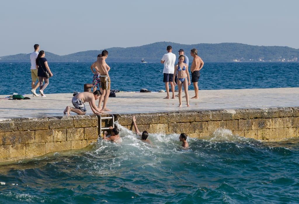Boys swimming in the waves off a dock in Zadar, Croatia