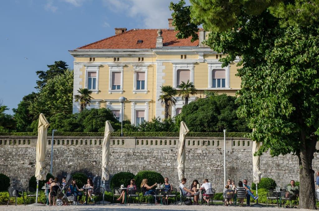 Street cafe scene in front of a yellow building in Zadar, Croatia.