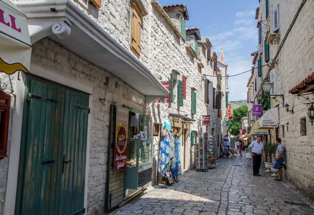 A small cobblestoned street edged with souvenir shops in Trogir, Croatia