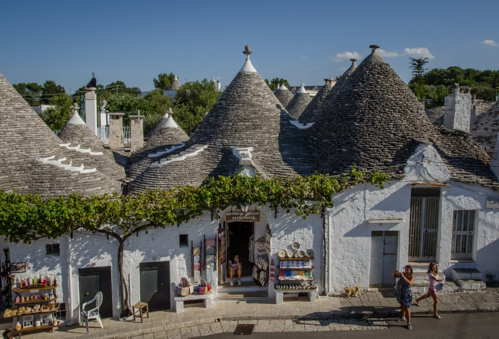 "White conical ""Trulli"" homes in Alberobello, Italy. Several homes are stuck together with gray shingled pointy roofs. A tree grows alongside a wall. Several doors have gift shops and two women are taking pictures of the houses."