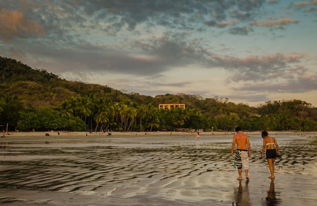 Two people walking on a gray beach underneath a blue sky with pink and gray clouds in Samara, Costa Rica.