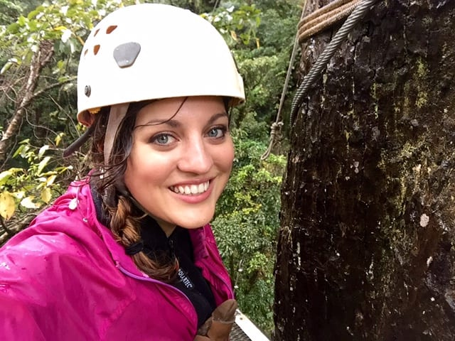Kate wearing a helmet and pink jacket while zip lining in Monteverde, Costa Rica