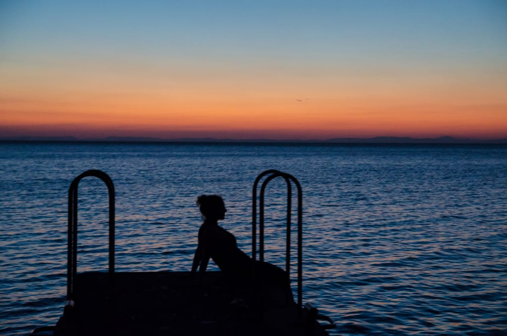 A silhouette of Kate against the blue lake and a red-to-blue sunset behind her.