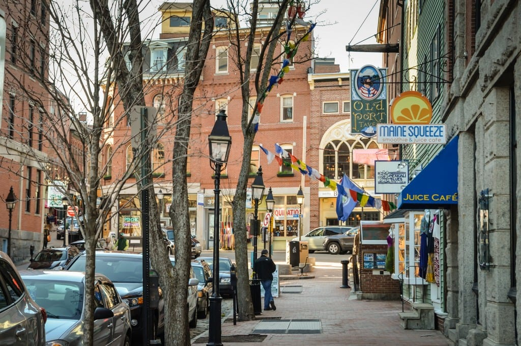 A street with boutiques on it in Portland, Maine, old-fashioned gas lamps on the street.