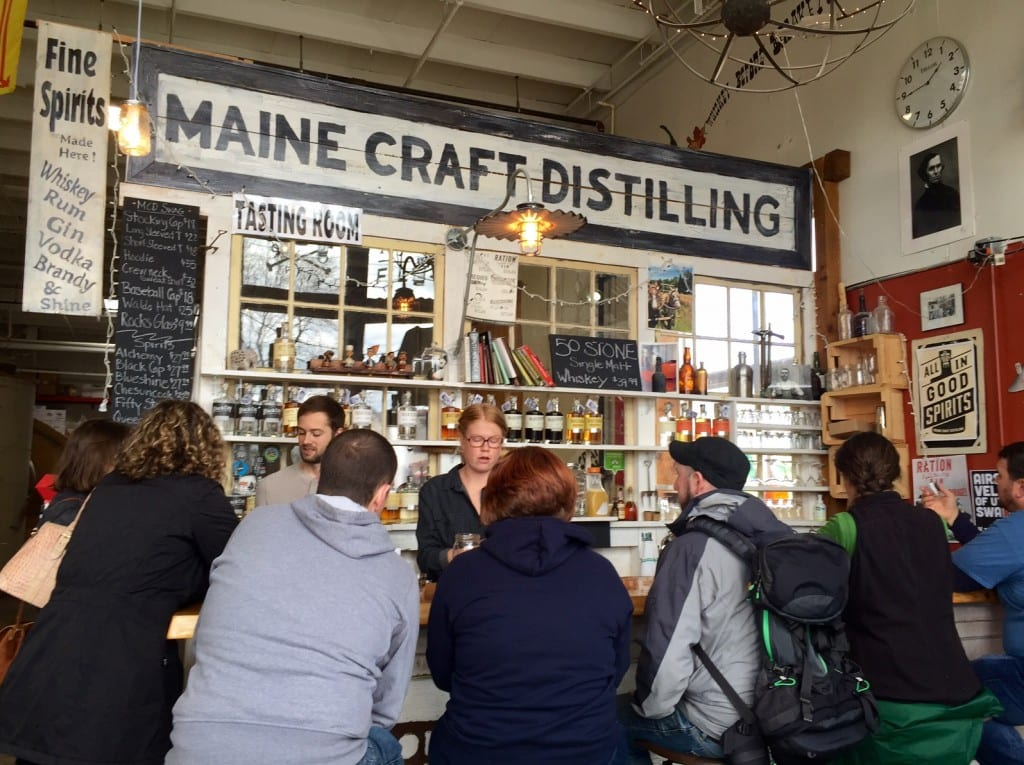 """A group of people in hoodies sitting at a bar with a big sign reading """"Maine Craft Distilling"""""""