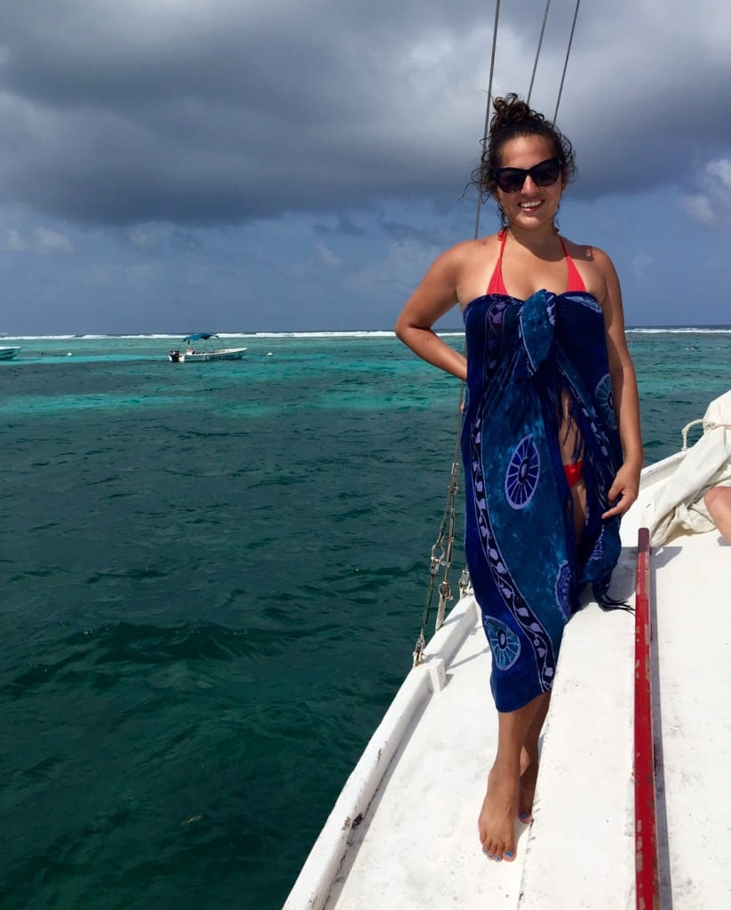Kate stands in a sarong on a boat on top of turquoise water.