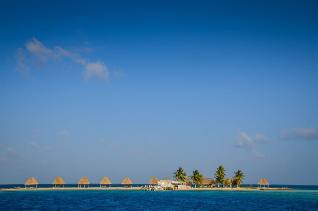 A tiny sandbar of an island topped with umbrellas and a few palm trees in Belize.
