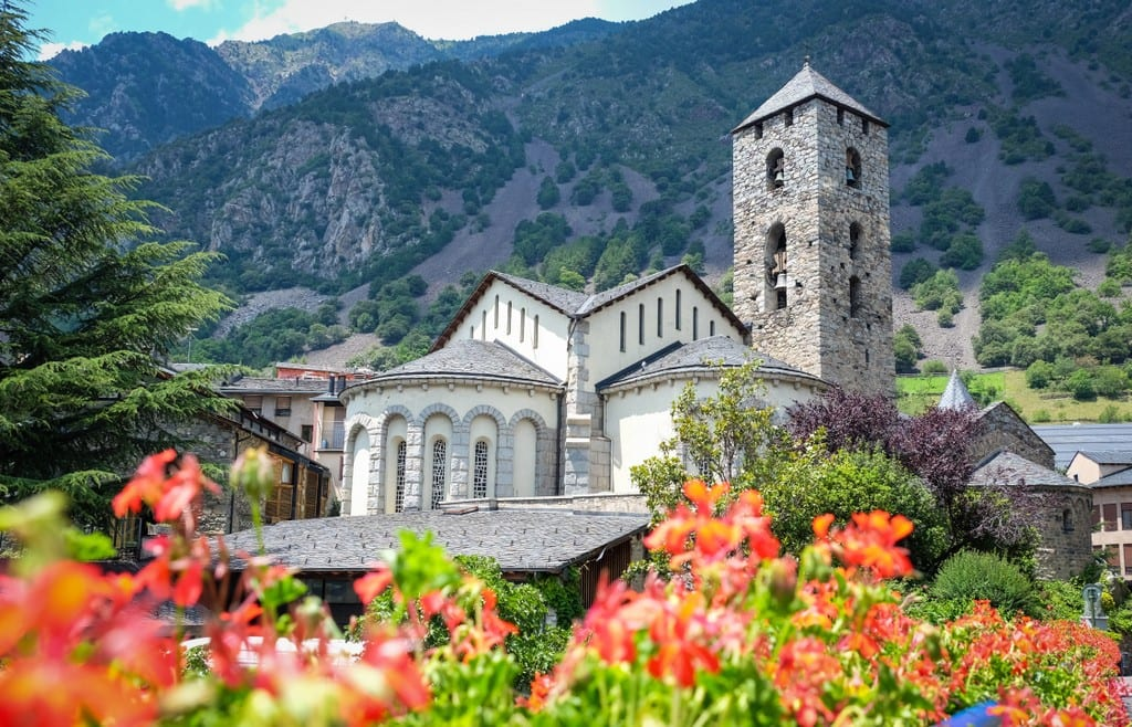 A church among the mountains of Andorra, bright red flowers in front.