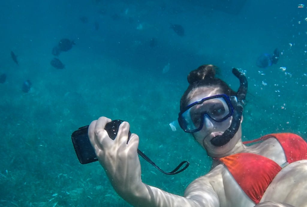 Kate taking a selfie underwater as she swims with sharks