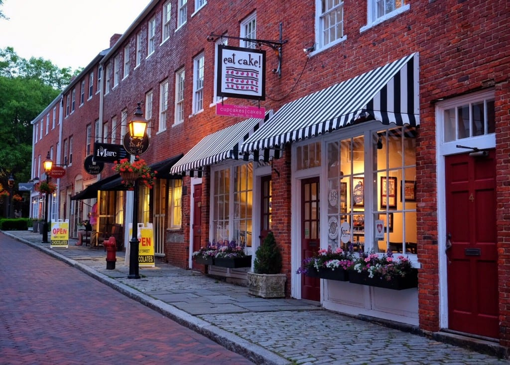 """A small street in Newburyport, Massachusetts, with brick roads, cobblestone sidewalks, and boutiques including a bakery with an """"Eat Cake"""" sign in a brick building."""