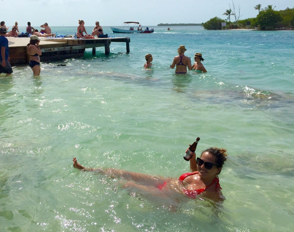 Kate swimming in the clear water at Caye Caulker with a beer in one hand