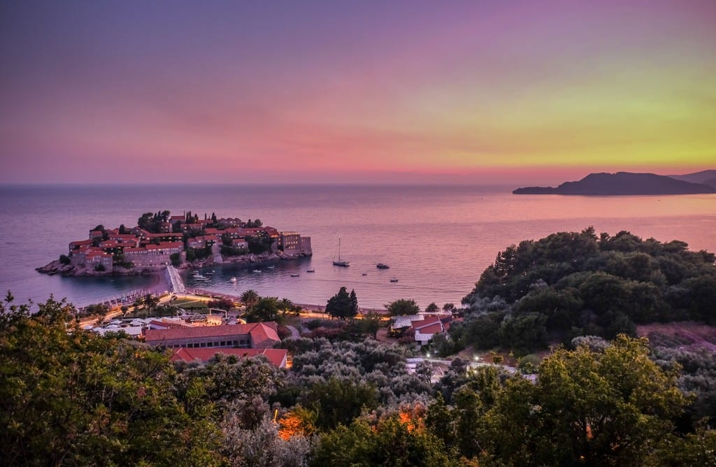 A bright pink and yellow sunset over the island of Sveti Stefan, just off the coast of Montenegro.