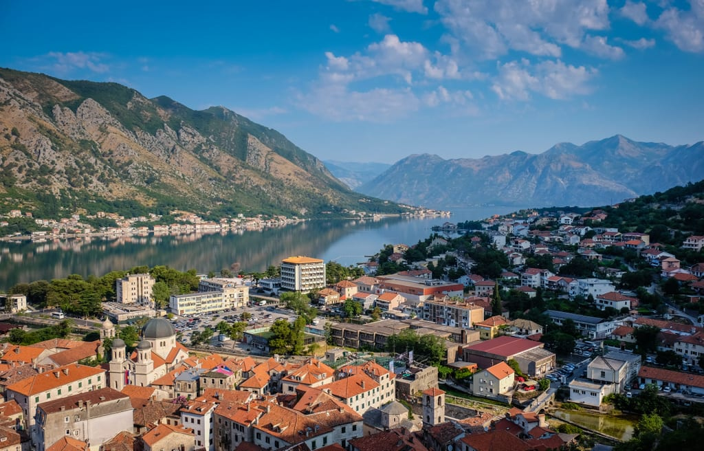 A sunrise over the Bay of Kotor, a fjord with green hills jutting into the glassy bay, buildings with orange roofs in the foreground.