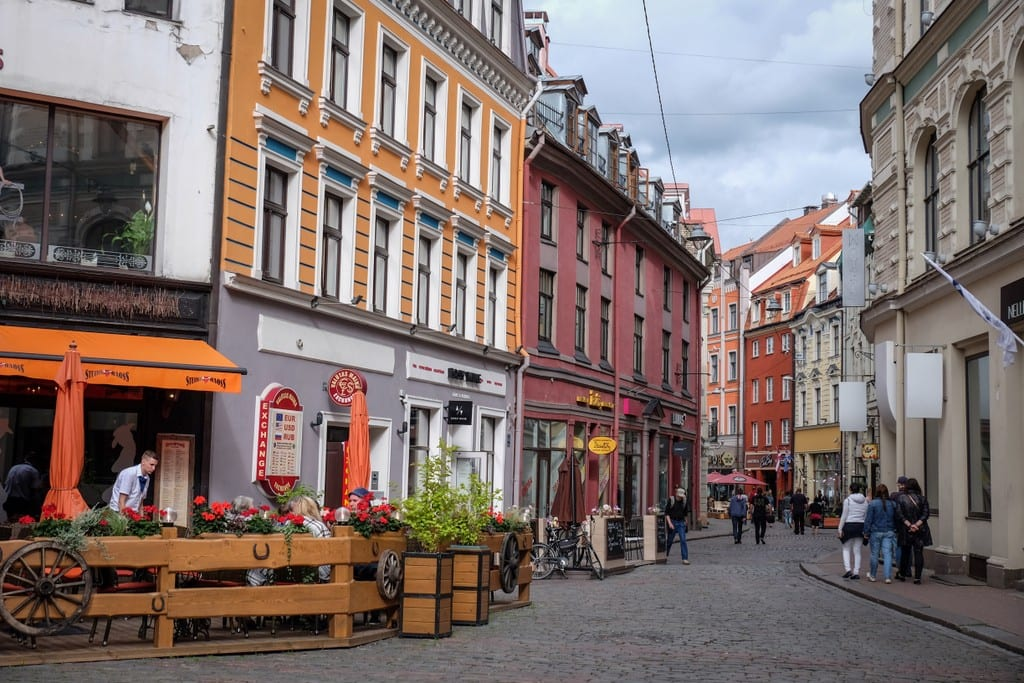 A narrow street in Riga lined with orange and pink buildings.