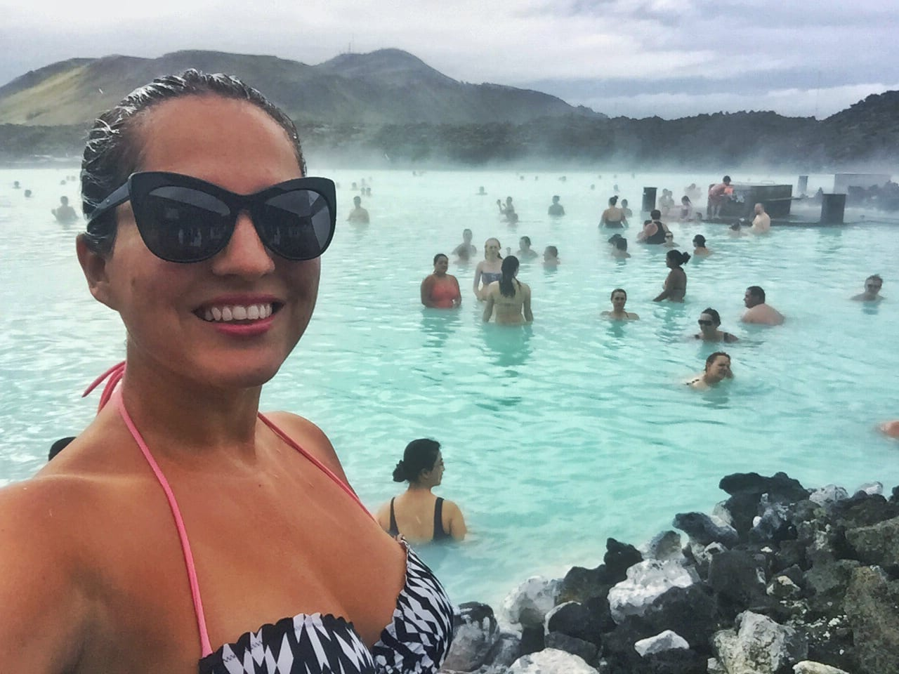 Kate takes a selfie in the Blue Lagoon in Iceland, steaming bright blue water behind her with people in the water.