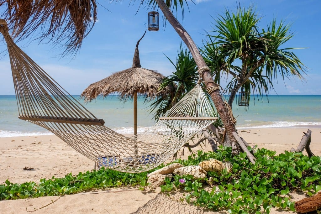 A hammock and straw umbrella palapa on Relax Bay, Koh Lanta, Thailand, clear turquoise water and the beach.